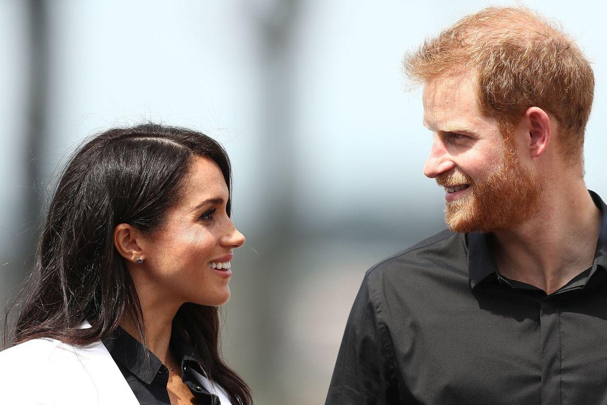 Prințul Harry, îmbrăcat într-o cămașă neagră, îi zâmbește soției sale, ce poartă o cămașă neagră și un sacou alb